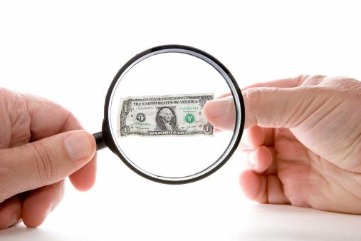 Looking at dollar bill wtih magnifying glass