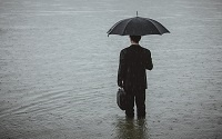 man with umbrella in flood